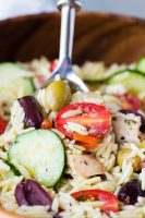 greek chicken orzo pasta salad in a brown bowl with a silver spoon.