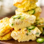 Jalapeno popper egg muffins stacked on a wooden cutting board