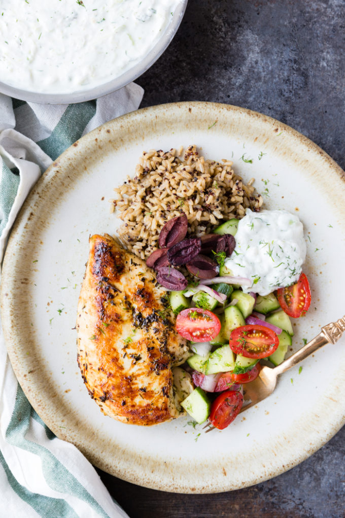 skillet greek chicken with bowl of yogurt in the back ground