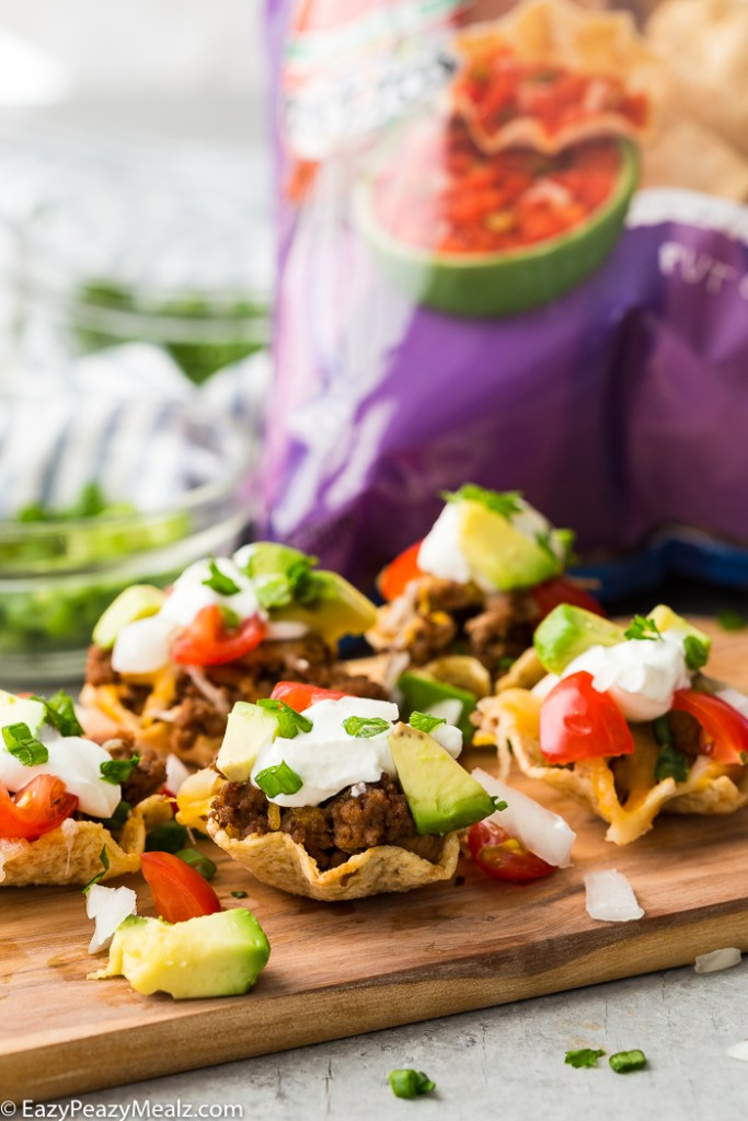 A cutting board with taco bites in Tostitos Scoops! a bag of chips in the background.