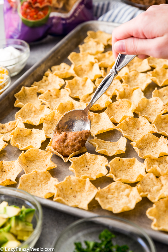 Adding refried beans to each chip