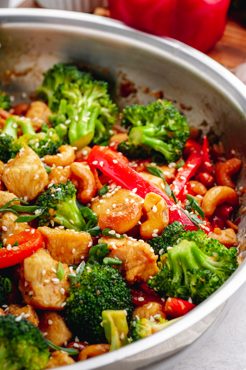 A stainless steel fry pan filled with broccoli, peppers, chicken, and cashew pieces, and topped with sesame seeds.