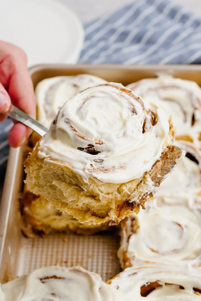 A pan of cinnamon rolls, taking a frosted cinnamon roll out of the pan.