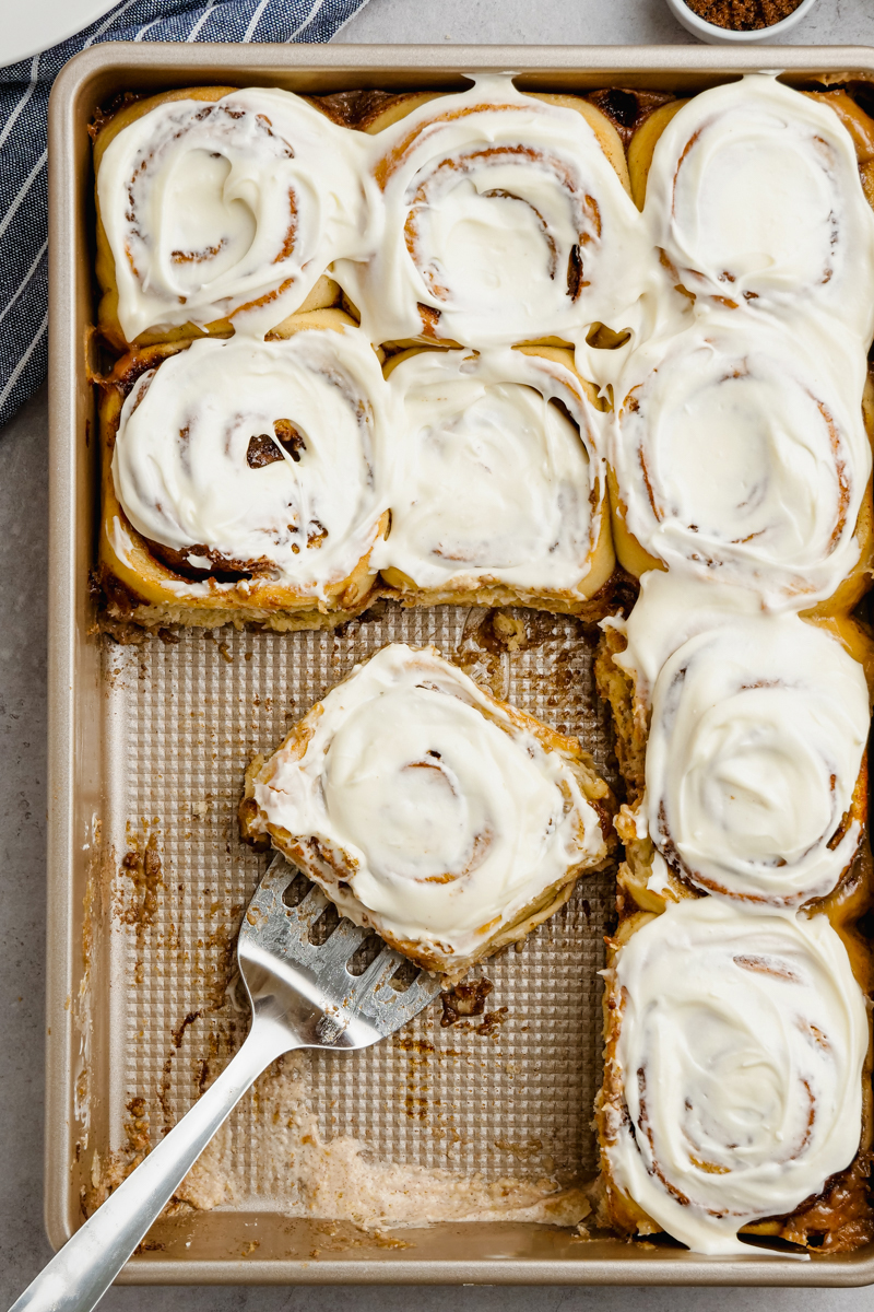 A pan of cinnamon rolls, some missing, a spatula with one frosted roll