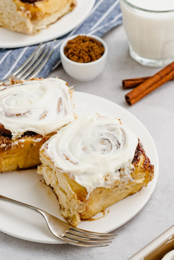 A plate with a fork and two cinnamon rolls
