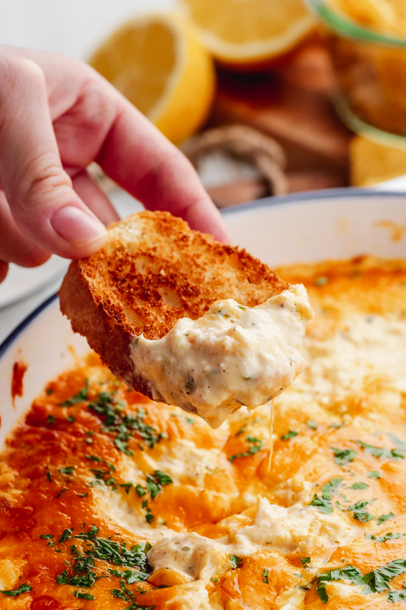A white casserole dish loaded with creamy crab dip, and a hand with a slice of baguette dipped into the crab dip.