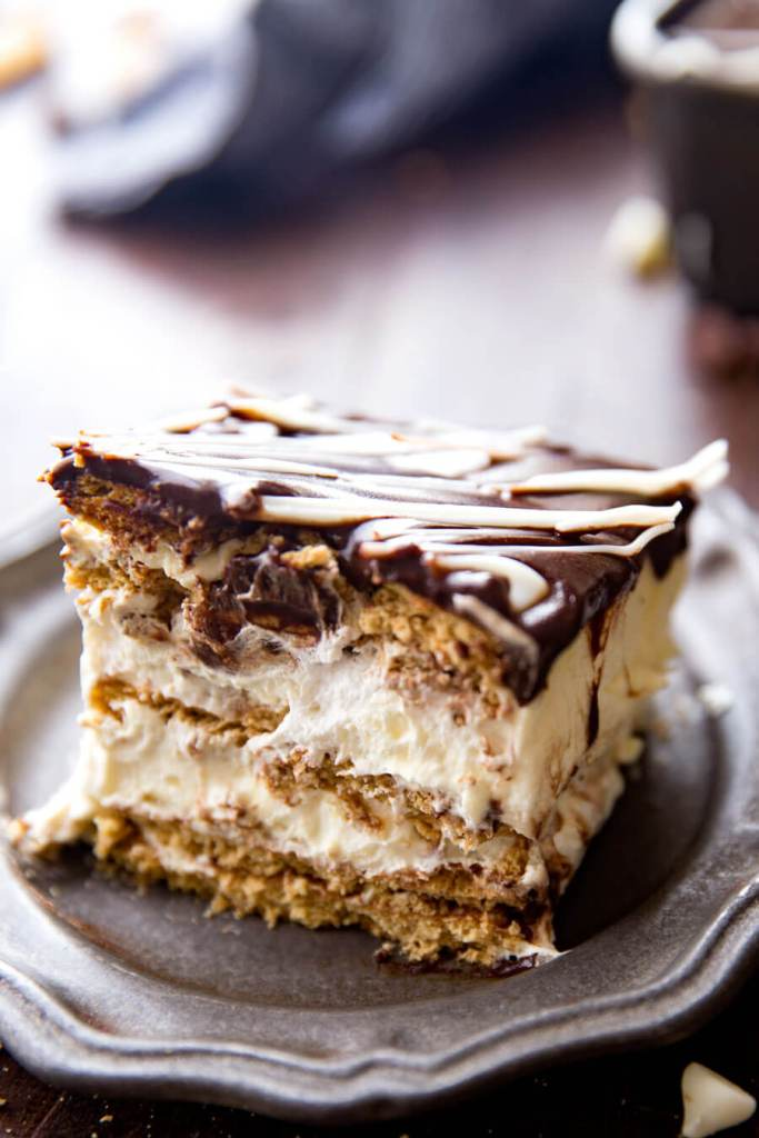 Simple Eclair Ice Box Cake: No baking, no fuss, this easy ice box cake is absolutely delicious and just so fun. Rich chocolate topping, fun vanilla custardy center, and graham crackers. It tastes like an eclair in cake form! And is way easier than baking eclairs.