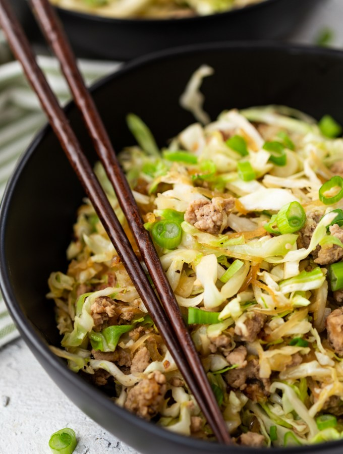 egg roll in a bowl, a black bowl with brown chopsticks. Pork and cabbage.