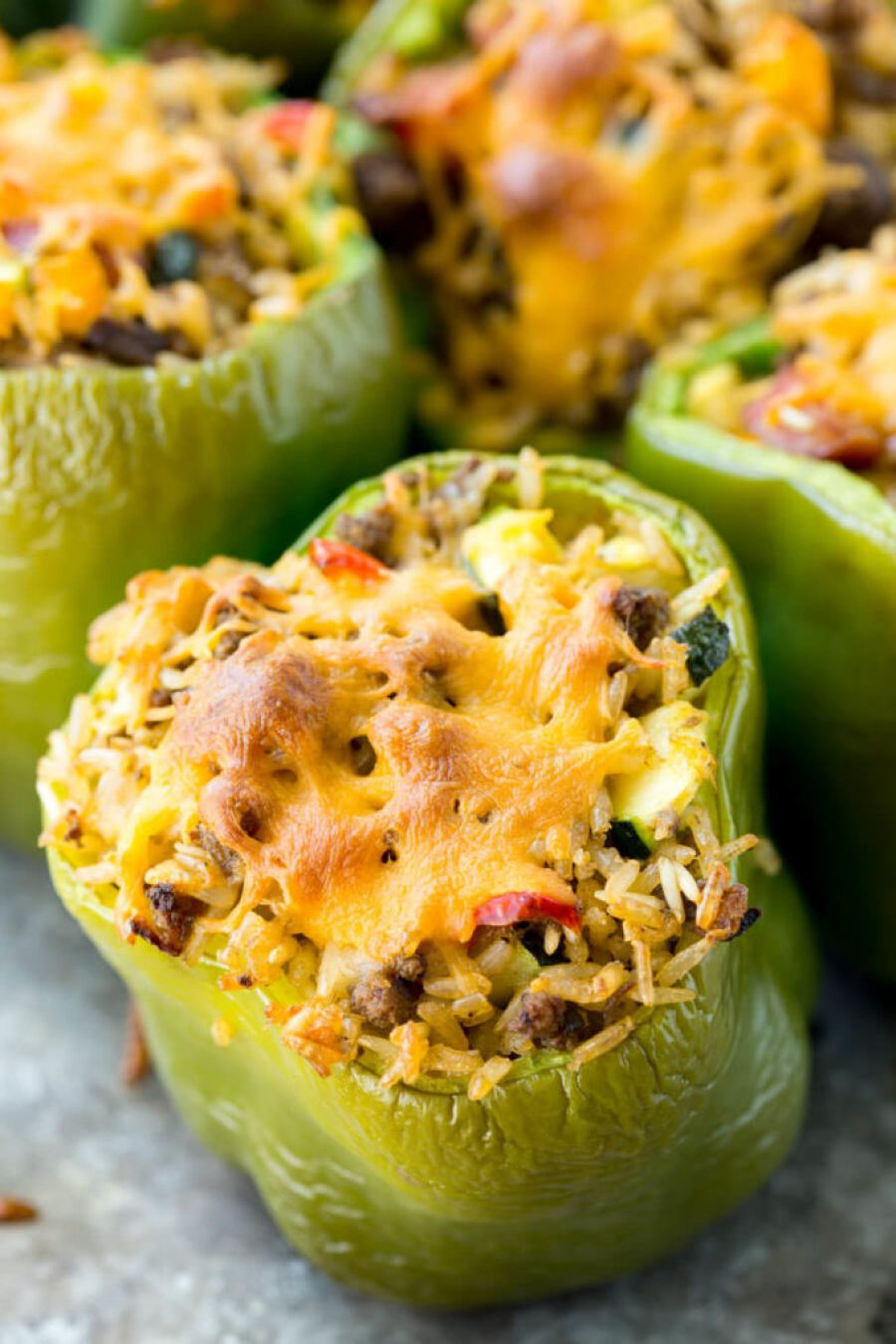 A green bell pepper stuffed with rice, sausage and veggies topped with crisp cheese