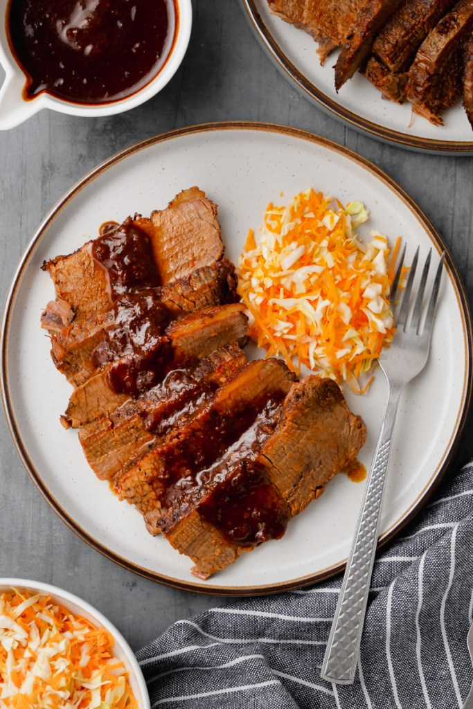 instant pot brisket on white plate with fork to the side and mashed potatoes