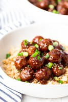 Mongolian beef meatballs in a white bowl on a bed of rice