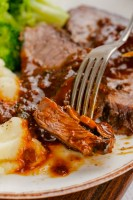 this delicious Instant Pot Sirloin Roast Beef with Mushroom Sauce on a white plate with fork into it with broccoli and mashed potatoes to the side.