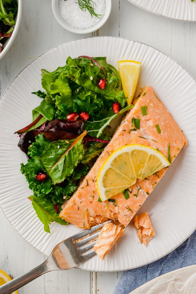 A white plate with oven poached salmon and lemon slices