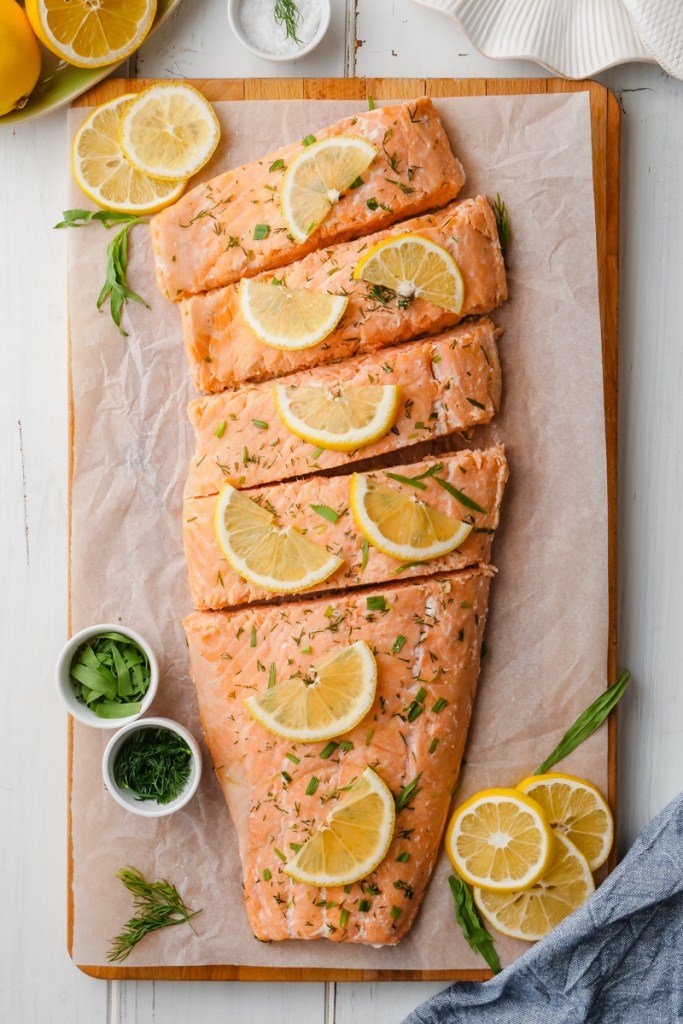 Oven poached salmon filet on a cutting board with lemons and dill