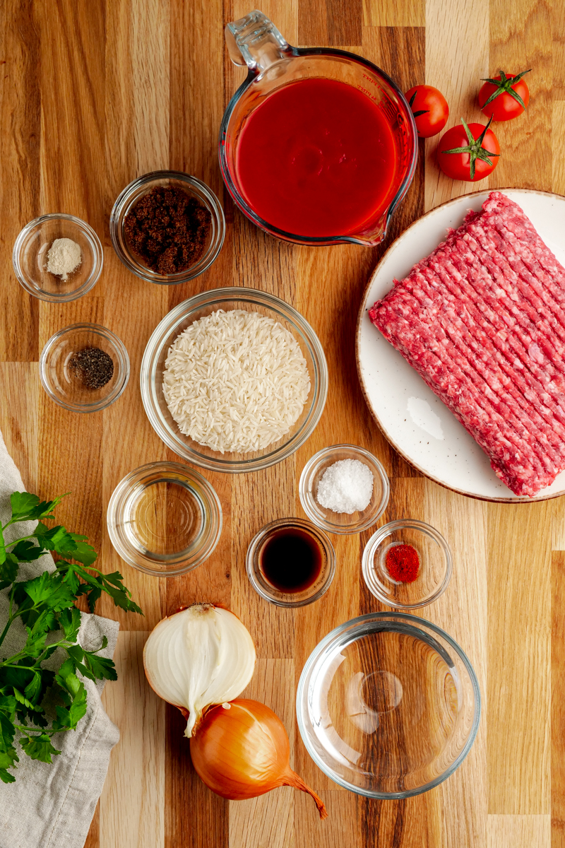 Ingredients for porcupine meatballs in little glass bowls, with ground beef on a white plate
