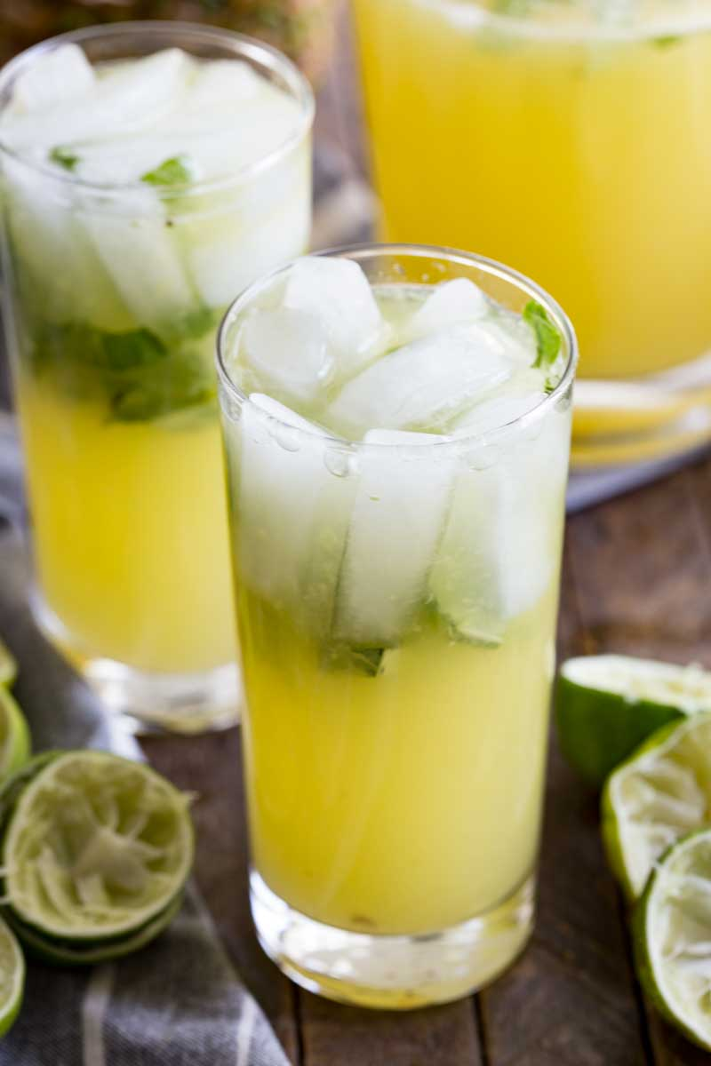 Tall glass of pineapple limeade with basil