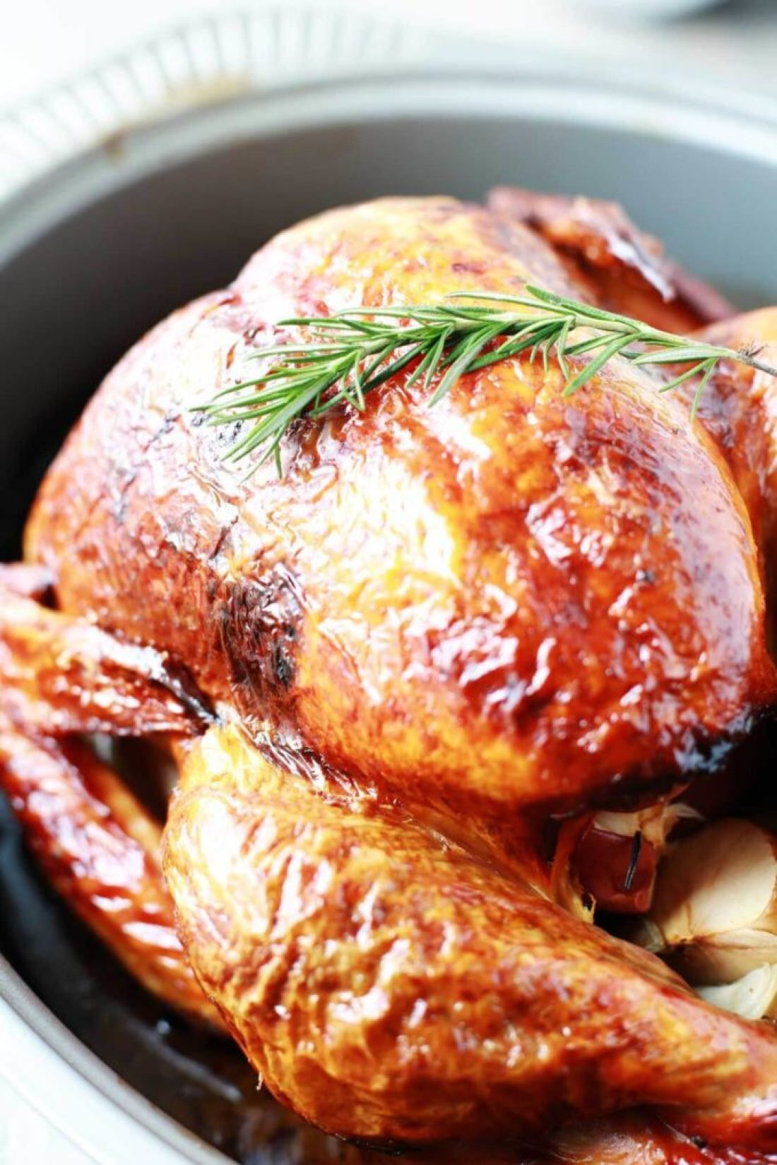 Juicy tender roasted turkey in roasting pan with rosemary for garnish