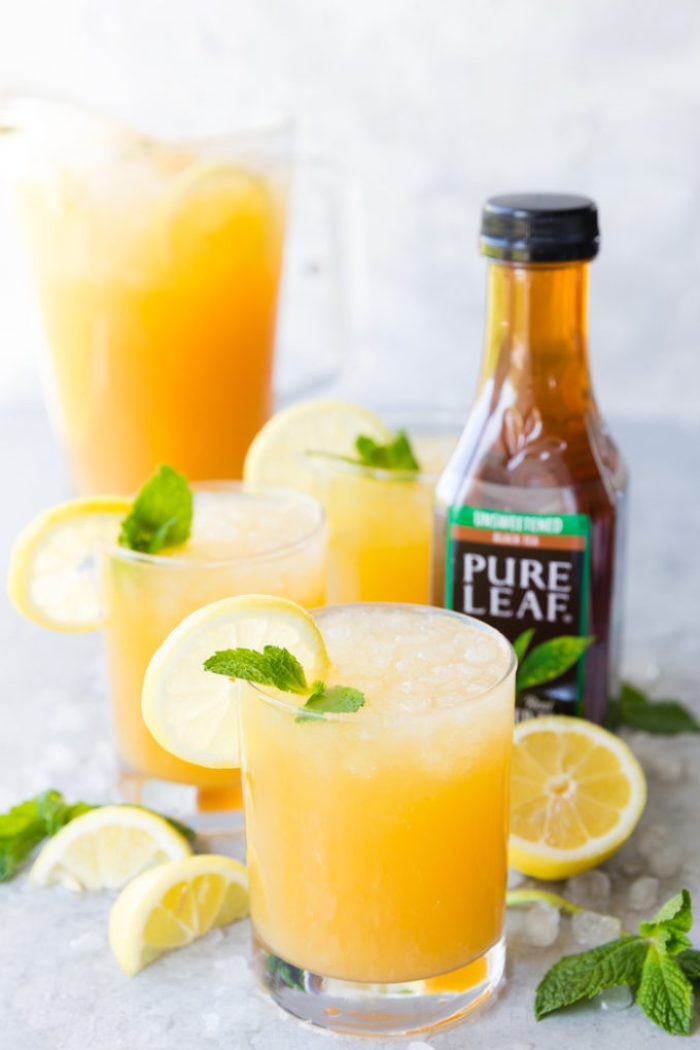 A few glasses of Mango Black Tea Lemonade with a lemon and mint garnish, and a pitcher of mango black tea lemonade in the background, as well as a bottle of Pure Leaf black tea on the side.