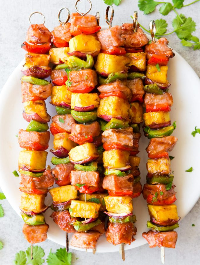 Deliciously sticky BBQ Pork Kabobs, with pineapple, green and red peppers, red onion, and bbq pork, topped with cilantro