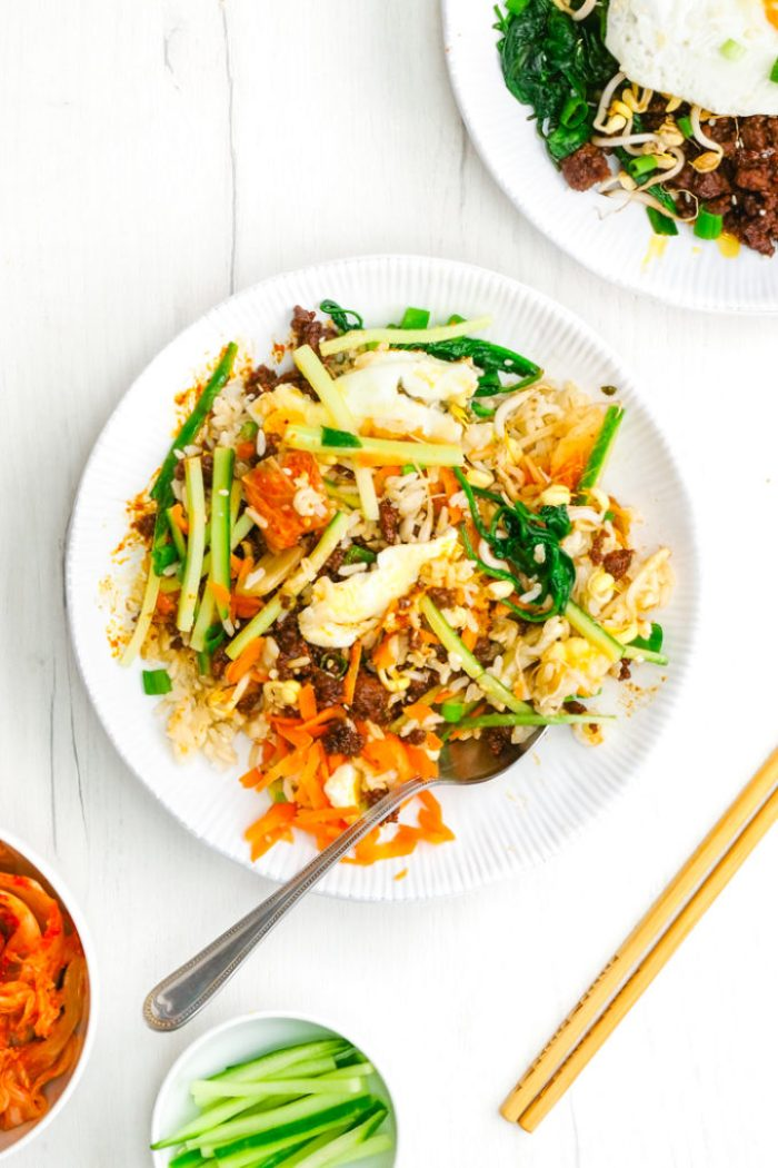 A mixed up Korean Beef Bibimbap on a white plate with chopsticks and a fork