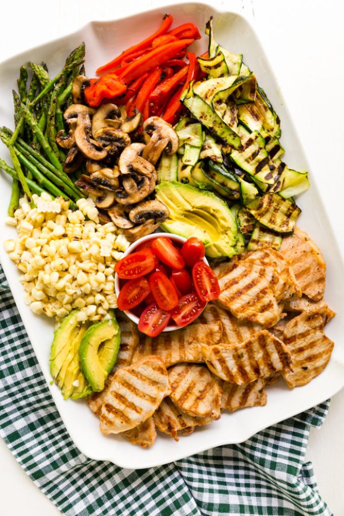 A platter of grilled pork, avocado, corn, tomatoes, asparagus, mushrooms, red pepper, and zucchini for grilled pork power bowls