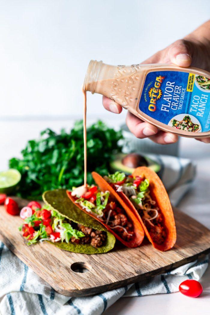 Ortega flavor craver sauce being poured onto ground beef tacos