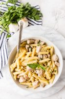 Roasted garlic and herb penne pasta in a white bowl with a blue and white napkin, cloves of garlic, and fresh parsley