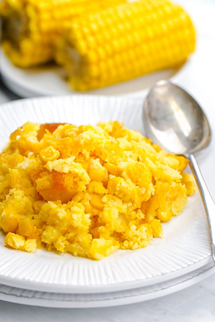 A delicious corn casserole, on a white plate with a silver spoon