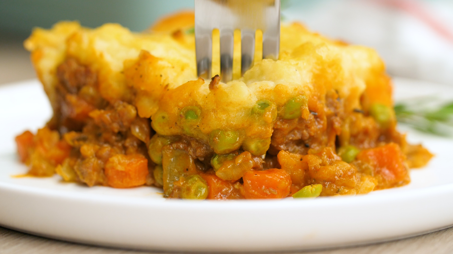 A front view of some shepherd's pie, with the ground lamb filling, and vegetables and potato layer, a fork sticking in the top