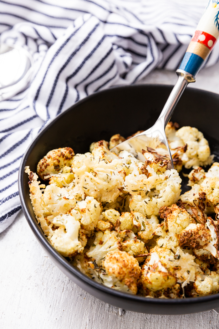 Air fryer roasted cauliflower in a black bowl with a spoon and striped napkin