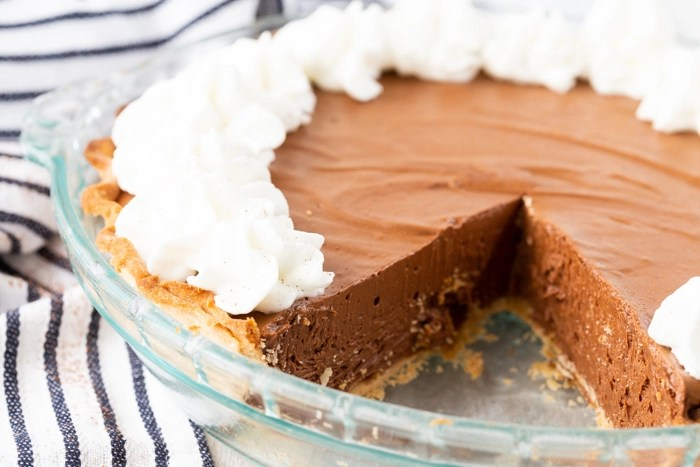 A whole chocolate pie, a slice out of the pie, and some whipped cream.
