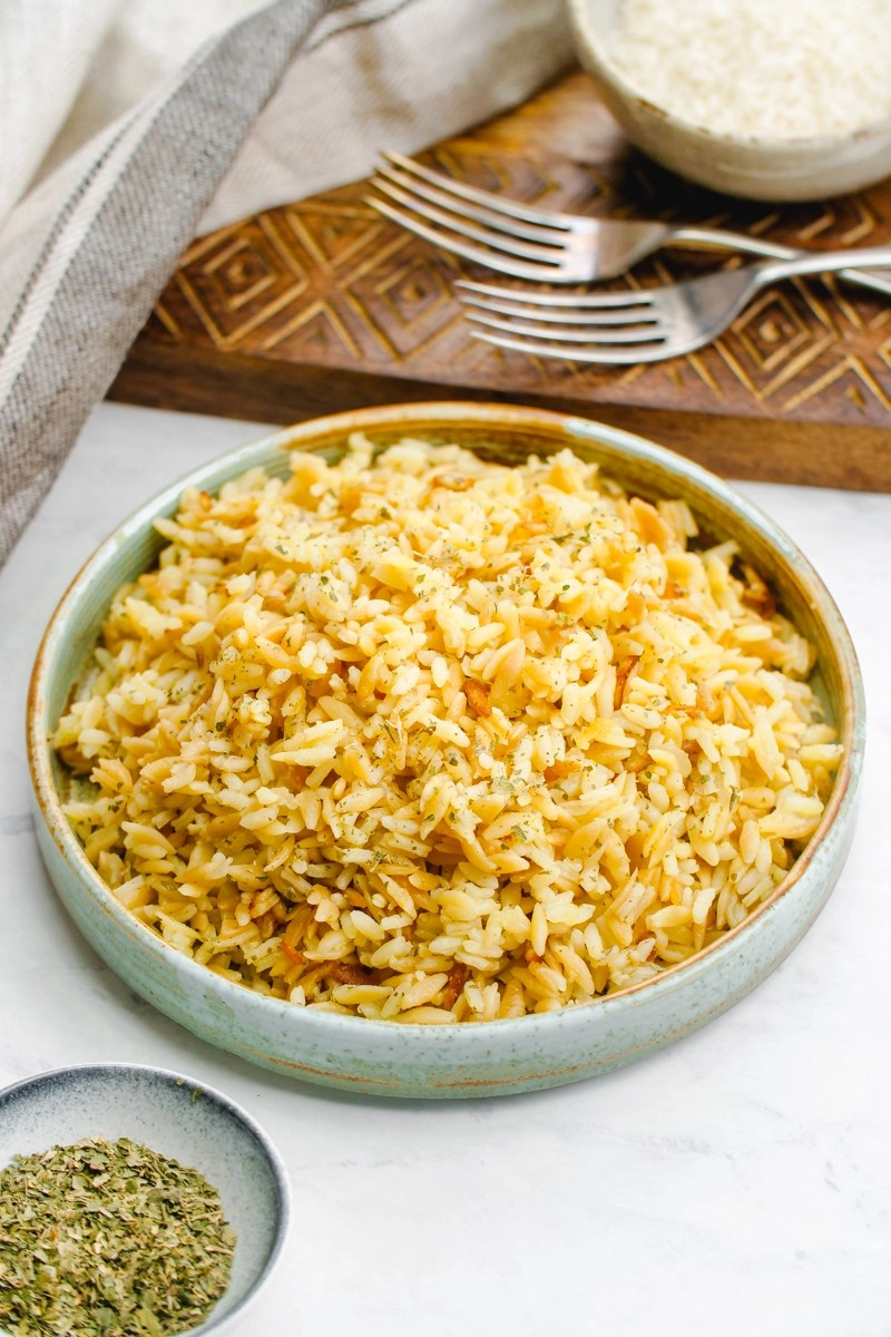 A beautiful bowl of rice pilaf with a cutting board and forks behind it