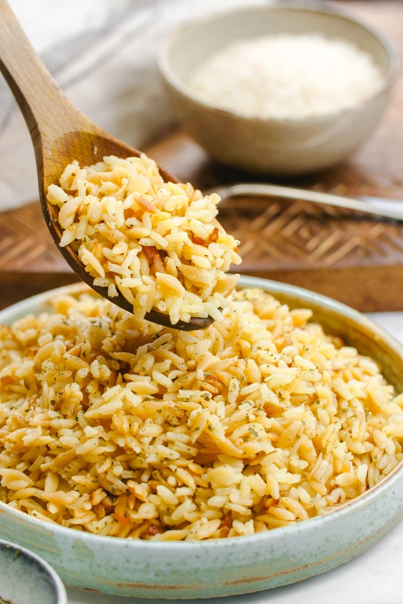 Easy to make rice pilaf in a bowl with a wooden spoon scooping some out