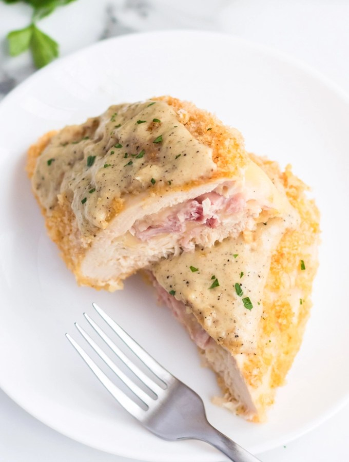 White plate with homemade chicken cordon bleu, cut in half, topped with a creamy sauce and garnish, fork resting on plate