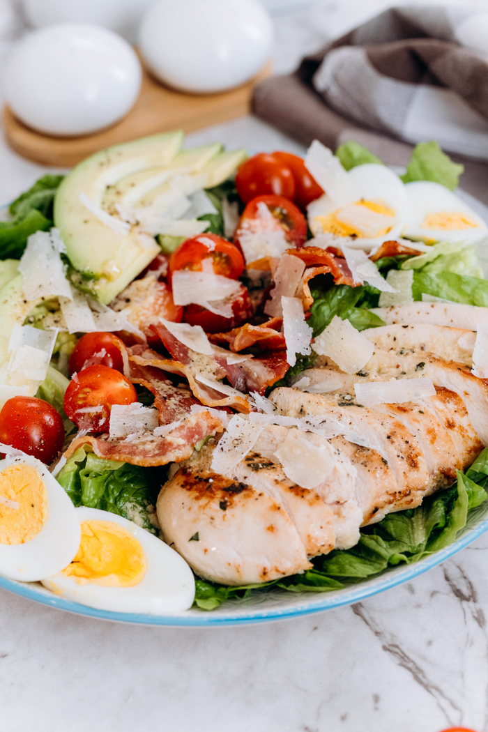 Chicken avocado caesar salad, a bed of lettuce topped with eggs, chicken, tomatoes, bacon, and avocados.