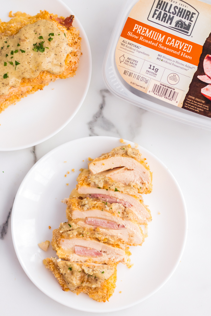 Chicken cordon bleu on a white plate, all sliced up.