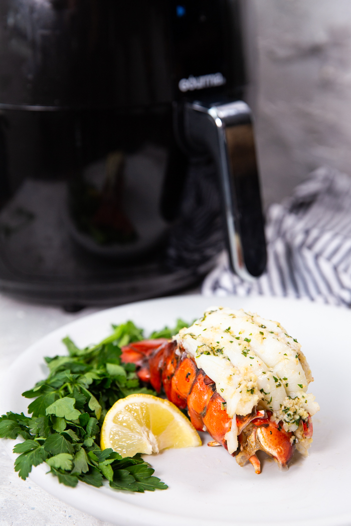 Air fryer lobster tail on a white plate with parsley and lemon wedge with an airfryer behind the plate