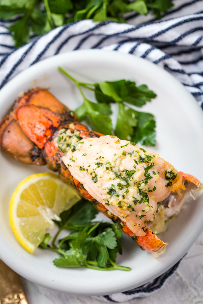 Broiled Lobster on a white plate with parsley and lemon wedge