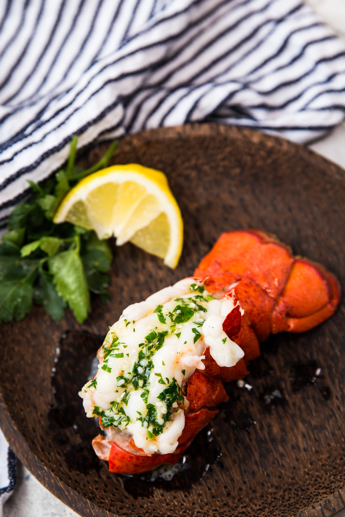 Steamed lobster tail on a wood plate with parsley and lemon wedges