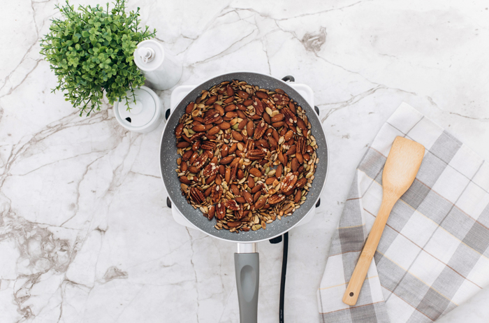 ingredients for keto granola all mixed up in pan with wood spatula