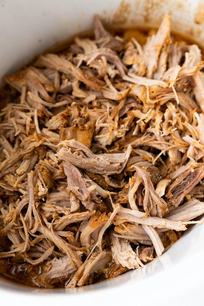 Sweet and Smoky roasted pork shredded and in a white crock pot