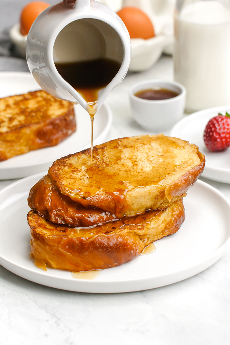 Classic french toast, a stack of two french toast slices with syrup being drizzled over the top.