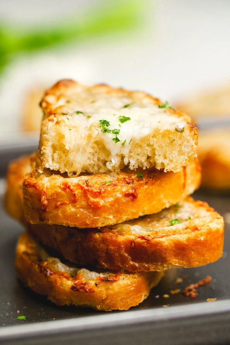 A stack of cheesy garlic bread with fresh parsley on top