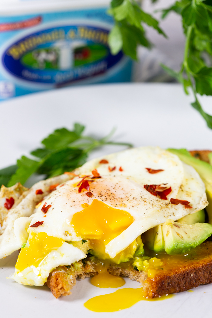 Avocado toast with a fried egg and chili pepper flakes