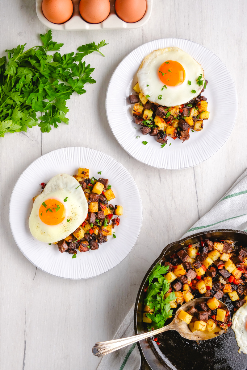 Two white plates topped with corned beef hash and eggs, with fresh parsley and eggs in the background