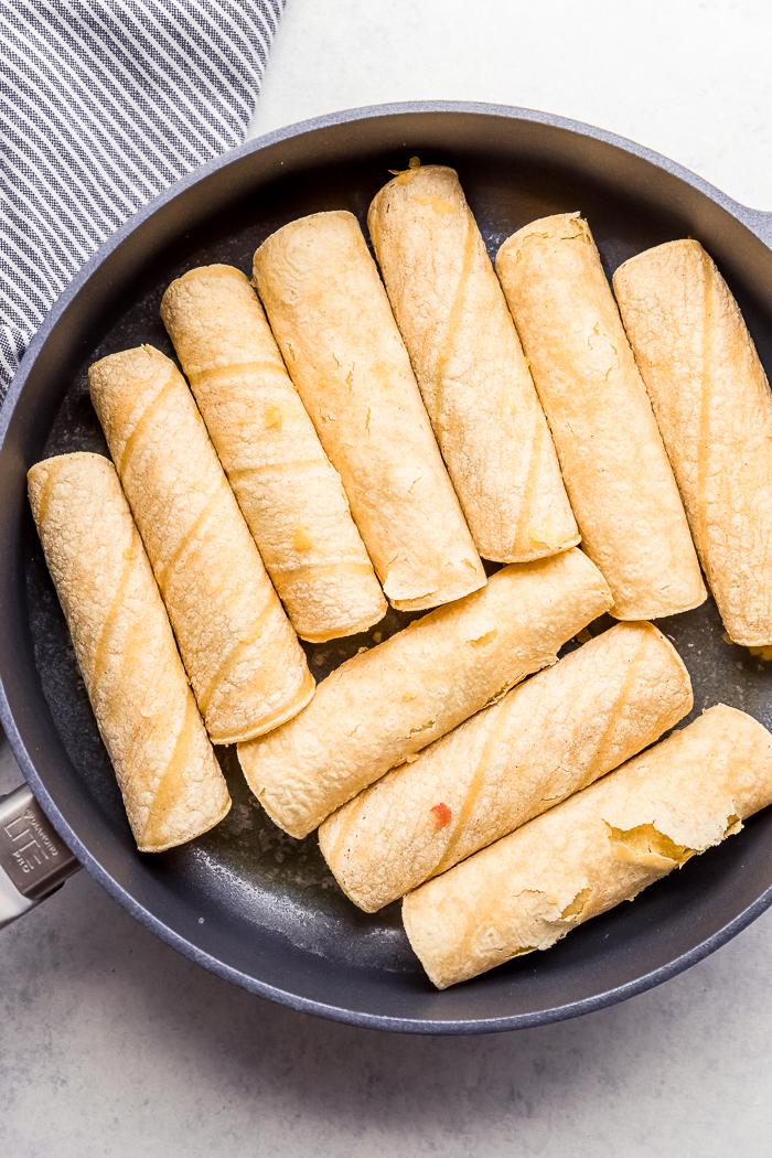 Corn tortilla taquitos in a skillet