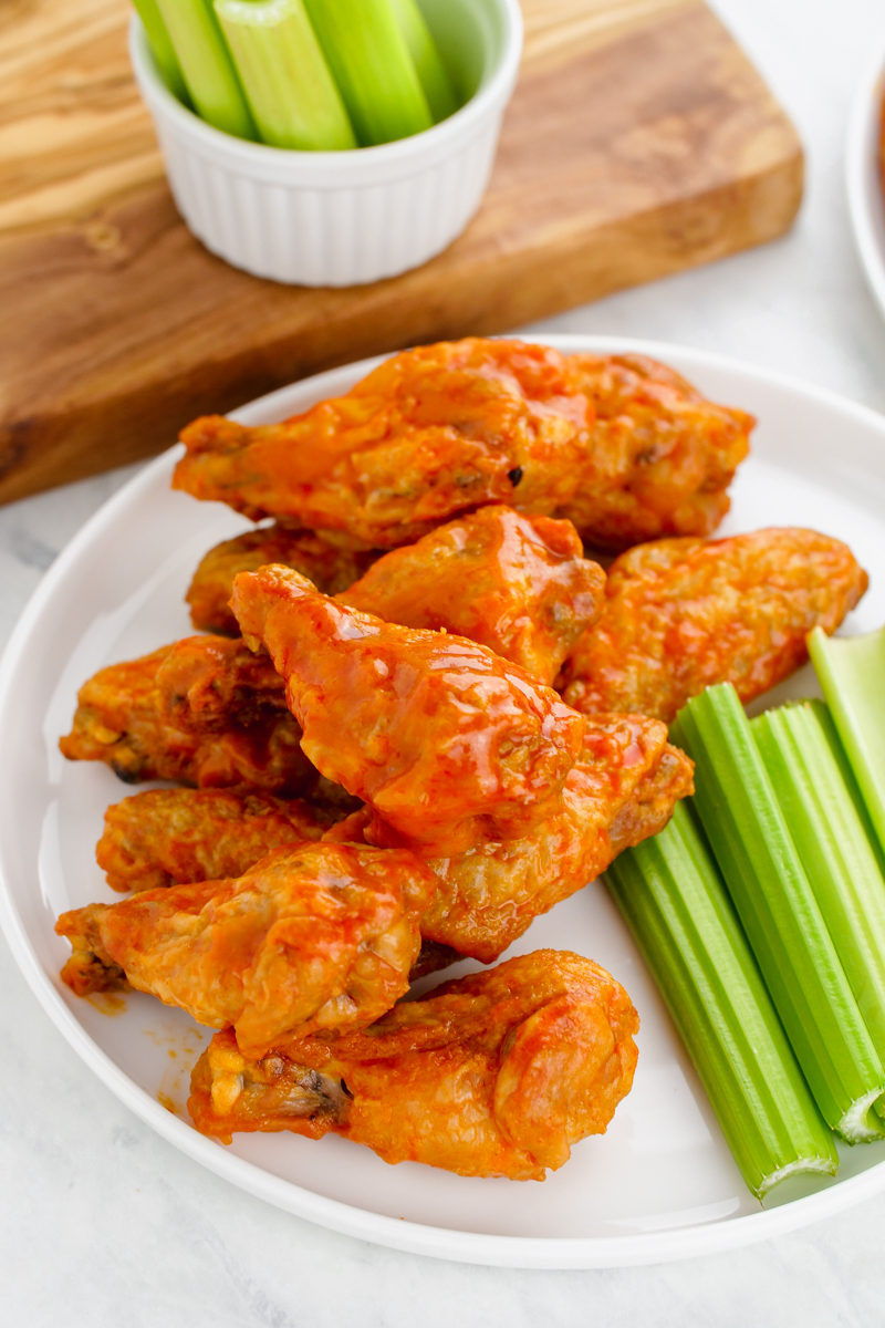 A plate of crispy buffalo wings and celery