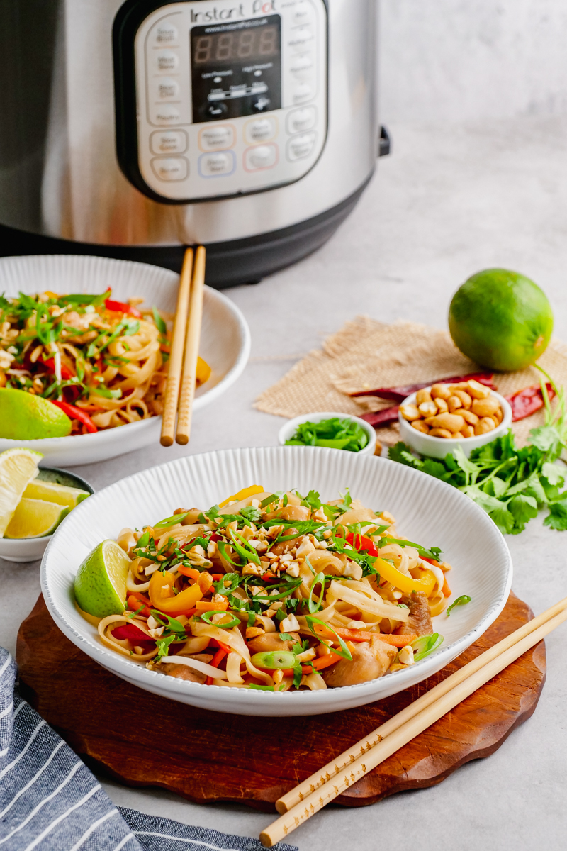 An instant pot in the background, bowls of pad thai and chop sticks, as well as garnish