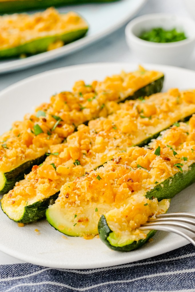 A white plate with three zucchini on it.