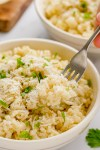 parmesan risotto in a white bowl with a fork